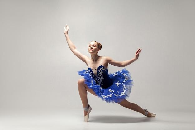 青いドレスと白い背景で優雅に分離して踊るトウシューズを身に着けているバレリーナ