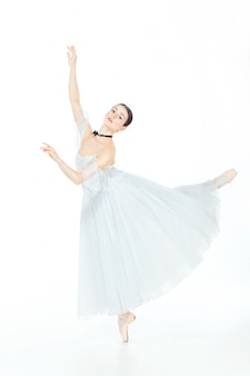 Ballerina in white dress posing on pointe shoes, studio background.