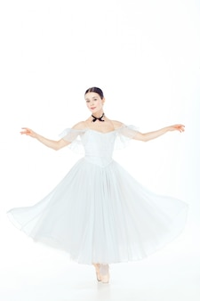 Ballerina in white dress posing on pointe shoes, studio space.