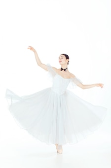 Ballerina in white dress posing on pointe shoes