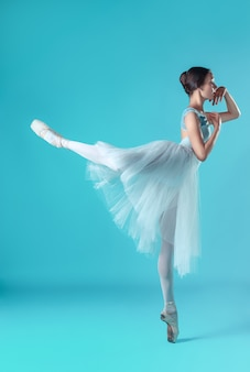 Ballerina in white dress posing on toes, studio background.