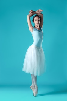 Ballerina in white dress posing on toes, studio space.