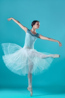 Ballerina in white dress posing on toes