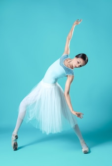 Ballerina in white dress posing on toes.