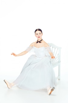 Ballerina in white dress sitting, studio space.