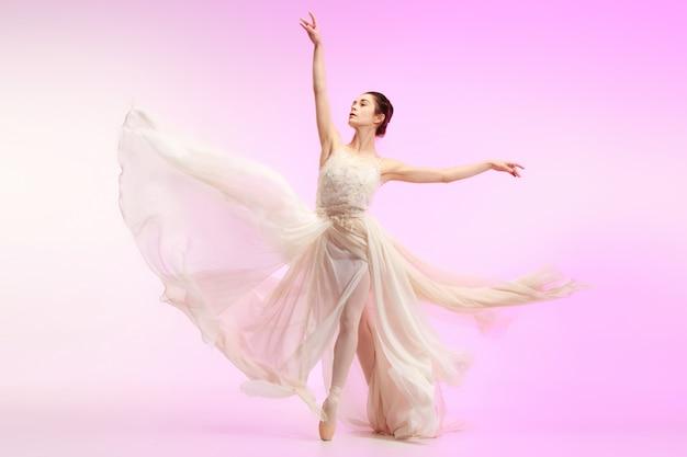 クラシックバレエのピンクのスタジオの美しさの上で踊るバレリーナ若い優雅な女性のバレエダンサー