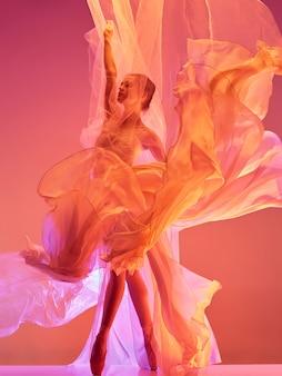 クラシックバレエの赤いスタジオの美しさの上で踊るバレリーナ若い優雅な女性のバレエダンサー