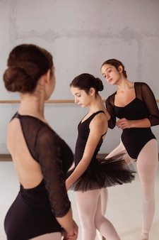 Ballerinas in tutu skirts and leotards preparing together for a performance