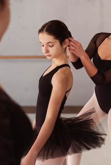 Ballerinas in tutu skirts preparing together for a performance