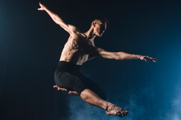 Ballerino dancing in tights with smoke