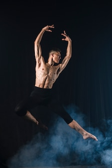 Ballerino posing in mid-air with tights