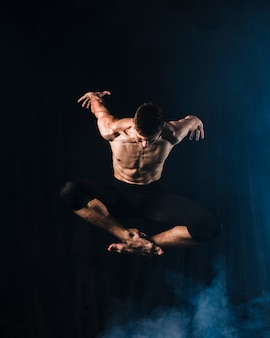 Ballerino in tights with crossed legs in mid-air