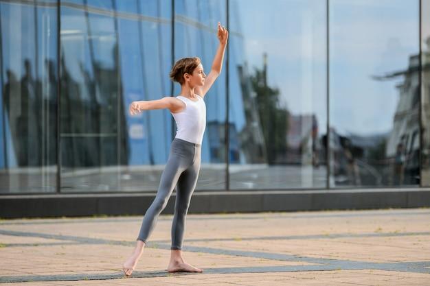 ガラスの壁に街と空の反射を背景に踊るバレエ少年ティーンエイジャー