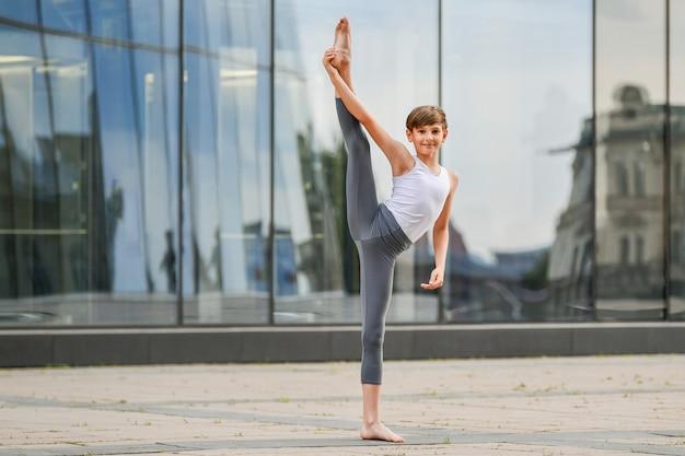 유리벽에 반사된 도시와 하늘을 배경으로 춤추는 발레 소년
