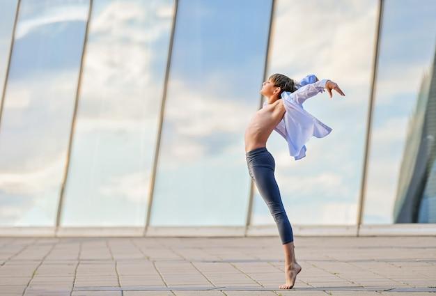 ガラスの壁の空の反射を背景に表情豊かに踊るバレエ少年ティーンエイジャー