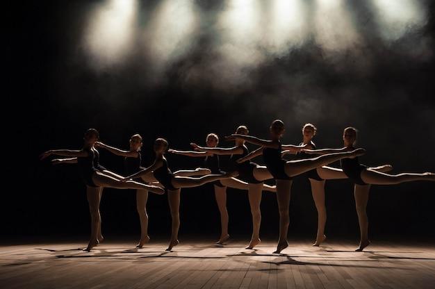 光と煙で劇場の舞台でバレエ教室。子供たちはステージで古典的な運動をしています。