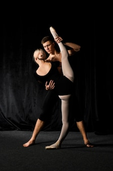 Ballet couple stretching in ballet outfits