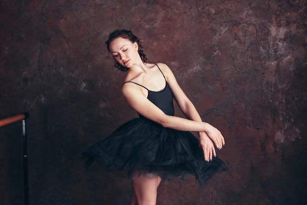 Ballet dancer ballerina in beautiful black dress tutu skirt posing in loft studio