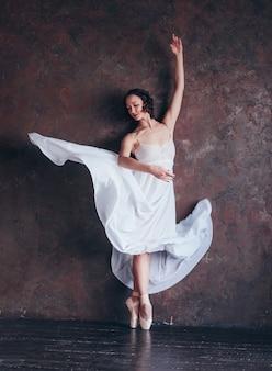 Ballet dancer ballerina in beautiful thin flying white dress is posing in dark loft studio