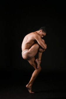 Ballet dancer embracing knee passionately