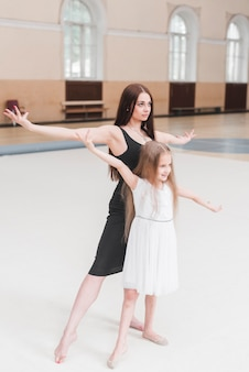 Ballet dancer and girl practicing in dance studio