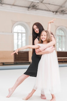 Ballet dancer hugging smiling cute girl practicing in dance studio
