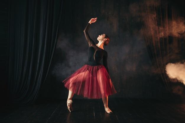 Артист балета в красном платье танцует на сцене театра. изящные тренировки балерины в классе