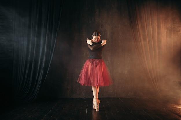 Артист балета в красном платье танцует на сцене