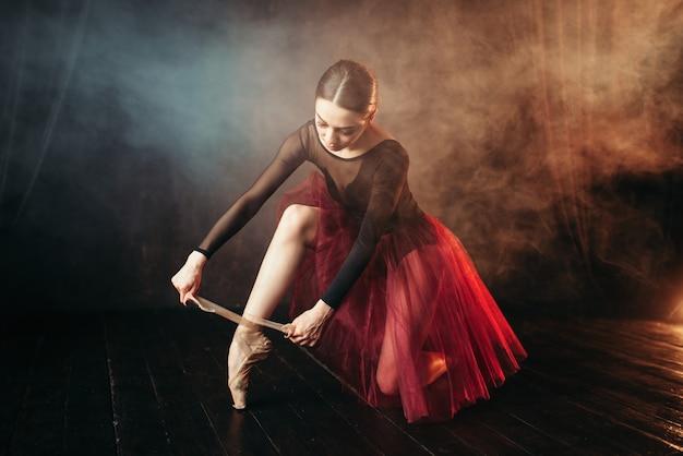 Артист балета в красном платье сидит на полу сцены в театре и завязывает пуанты. тренировка балерины элегантности в классе