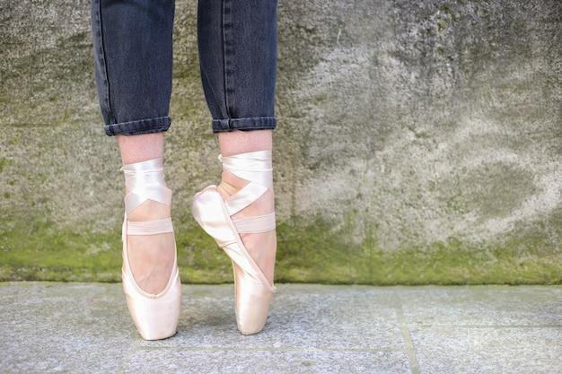 Ballet dancer legs in ballet shoes outdoors