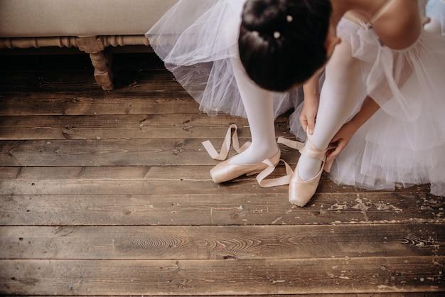 スタジオの床にバレエダンサーの足。 10代のダンサーは、バレエポワントシューズcopyspaceを置きます。