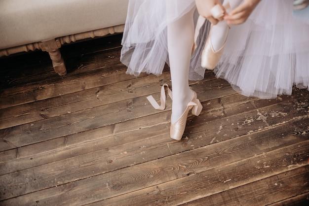 スタジオの床にバレエダンサーの足。 10代のダンサーがバレエポワントシューズを履く