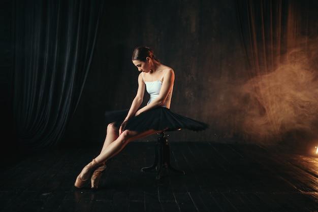 Артист балета сидит на черной банкетке на сцене театра. изящные тренировки балерины в классе