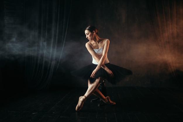 Артист балета сидит на черной банкетке