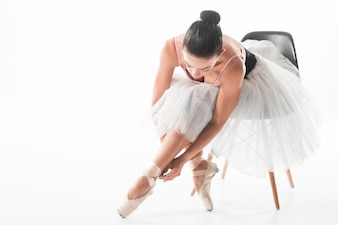 Ballet dancer sitting on chair tying ballet shoes against white background