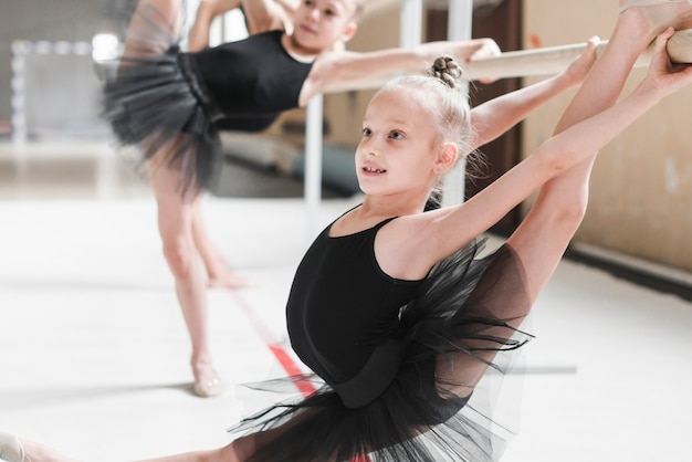 Ballet dancer stretching her legs on barre