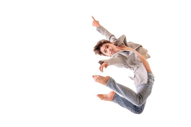 バレエダンサーの10代の少年が裸足でジャンプし、白いスペースに隔離します。