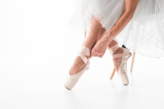 Ballet dancer tying ballet shoes