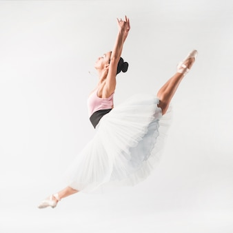 Ballet dancer wearing tutu posing in front of white backdrop