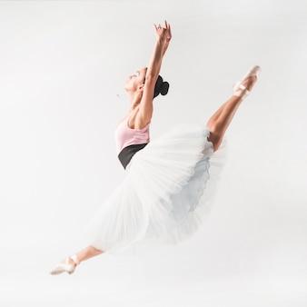Ballet dancer wearing tutu posing in front of white backdrop