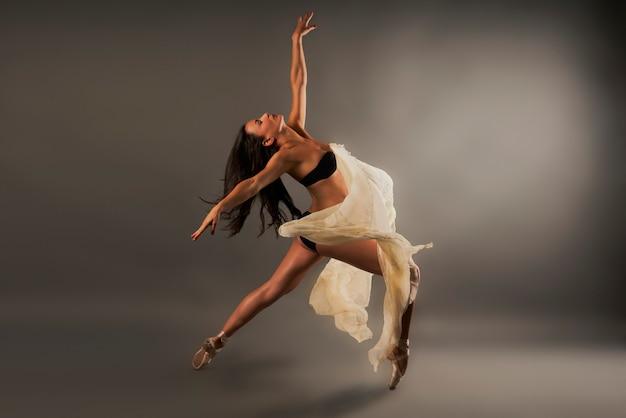 Балерина в черном белье и марле, покрывающей ее, делает танцевальную позу