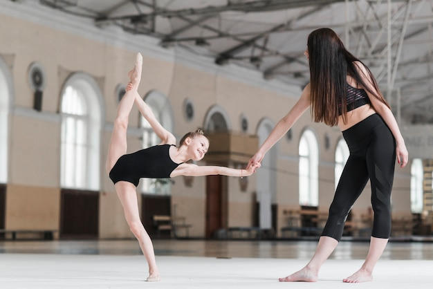 Ballet instructor helping young ballerina with ballet position