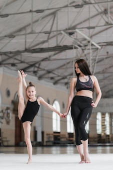 Ballet instructor holding young ballerina's hand in dance class