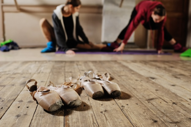 Ballet pointe close-ups against the background of young dancers who warm up and stretch before training in ballet class