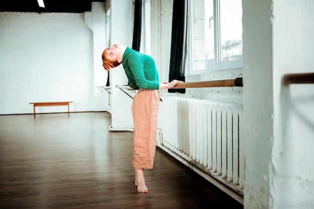 Балетная школа. рыжая профессиональная балерина с пучком волос стоит возле балетной стойки во время тренировки
