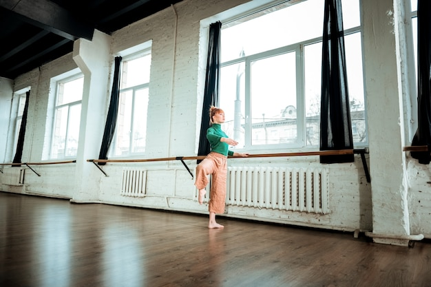 Ballet school. young professional modern dancer with red hair looking serious while training near ballet bar
