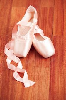 나무 바닥에 발레 신발입니다.