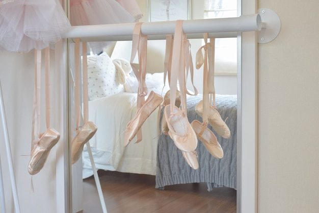 Ballet shoes hang on bar in bedroom