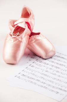 음악 점수 위에 흰색 바닥에 발레 신발.