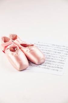 음악 점수 위에 흰색 표면에 발레 신발.
